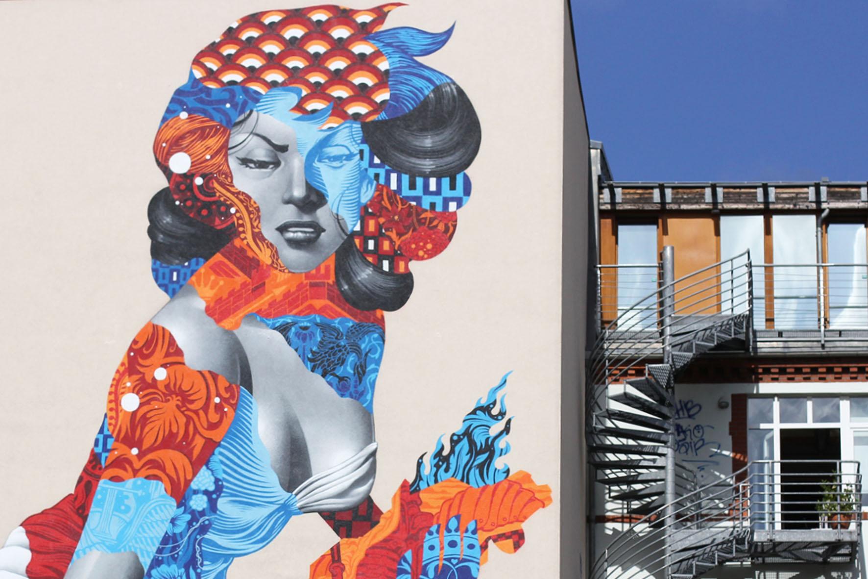 Eine Nahaufnahme des Street Art Murals Attack of the 50 Foot Socialite von Tristan Eaton auf einem Wohngebäude am Am Friedrichshain 33 in Berlin
