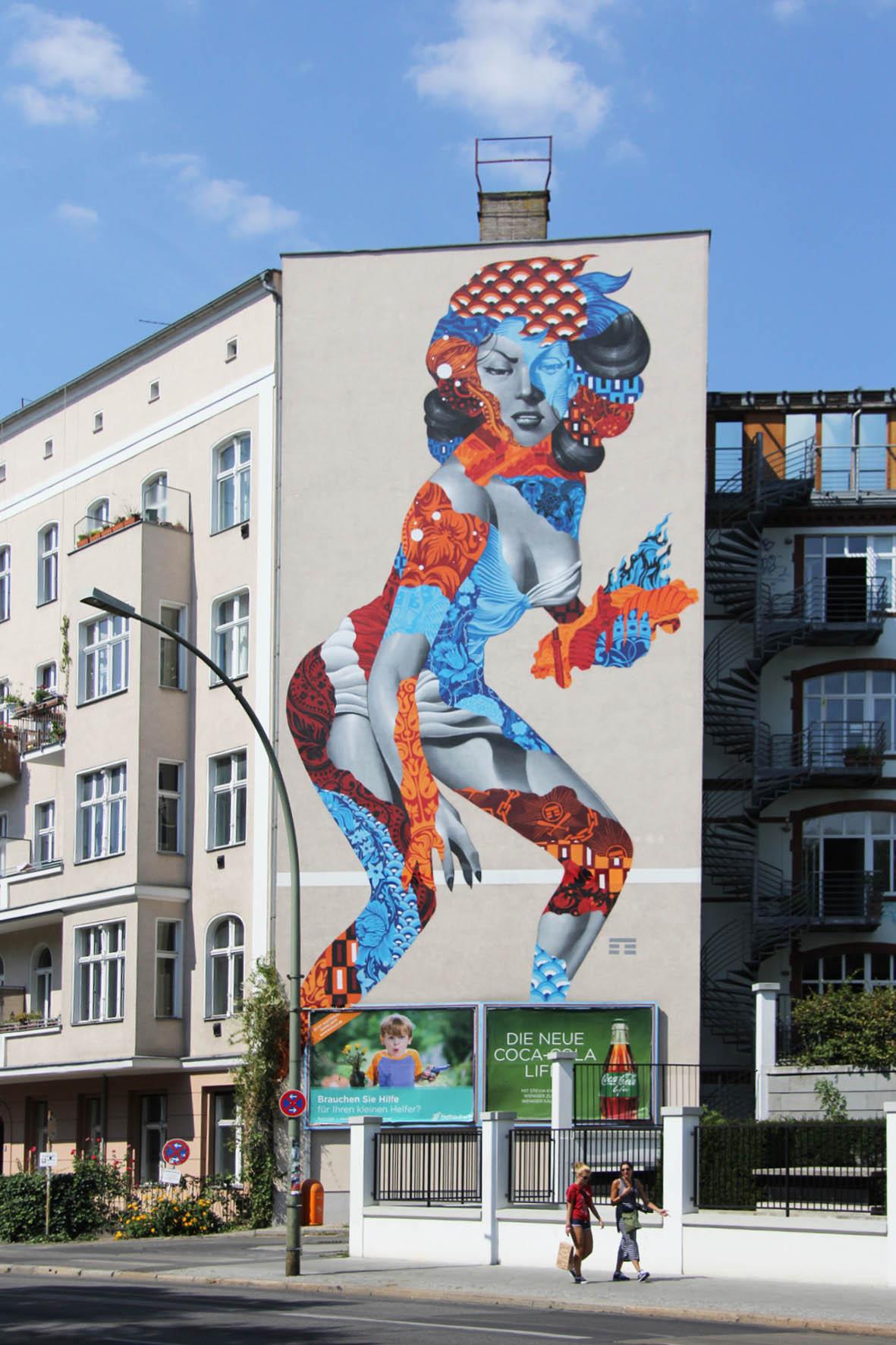 Das Street Art Mural Attack of the 50 Foot Socialite von Tristan Eaton auf einem Wohngebäude am Am Friedrichshain 33 in Berlin überragt die vorbeilaufenden Fußgänger