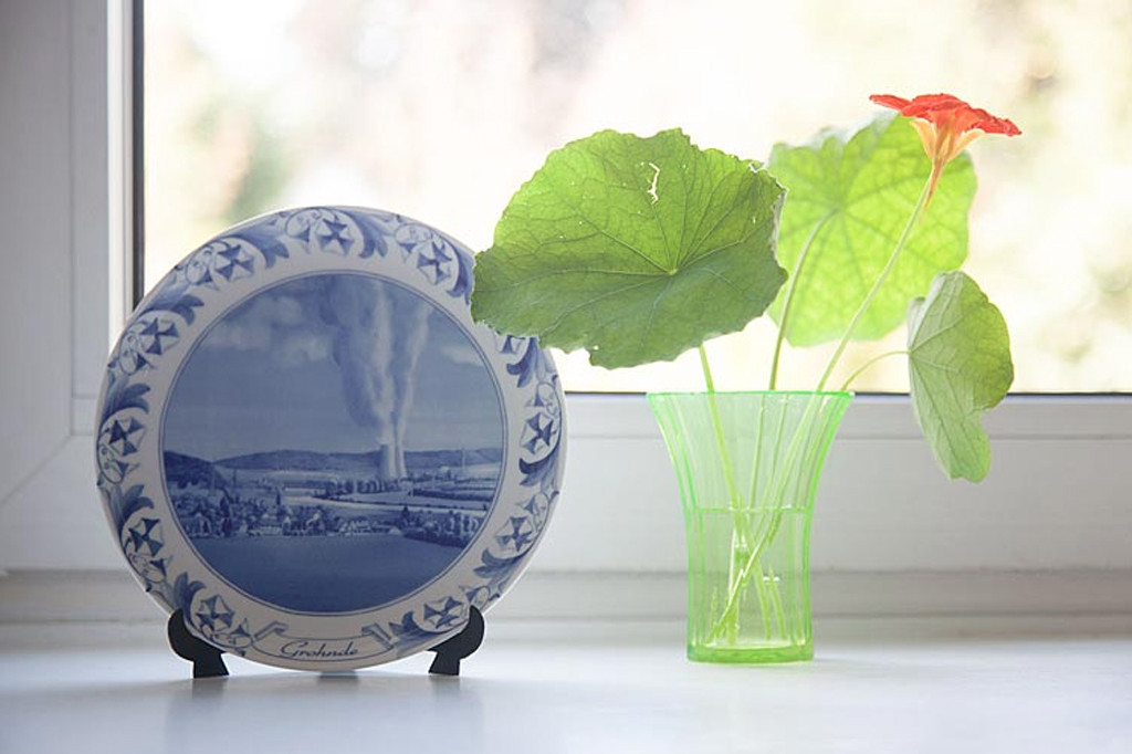 A display suggestion for a plate from Atomteller, a range of porcelain wall plates with blue and white designs of German nuclear power plants in idyllic landscapes