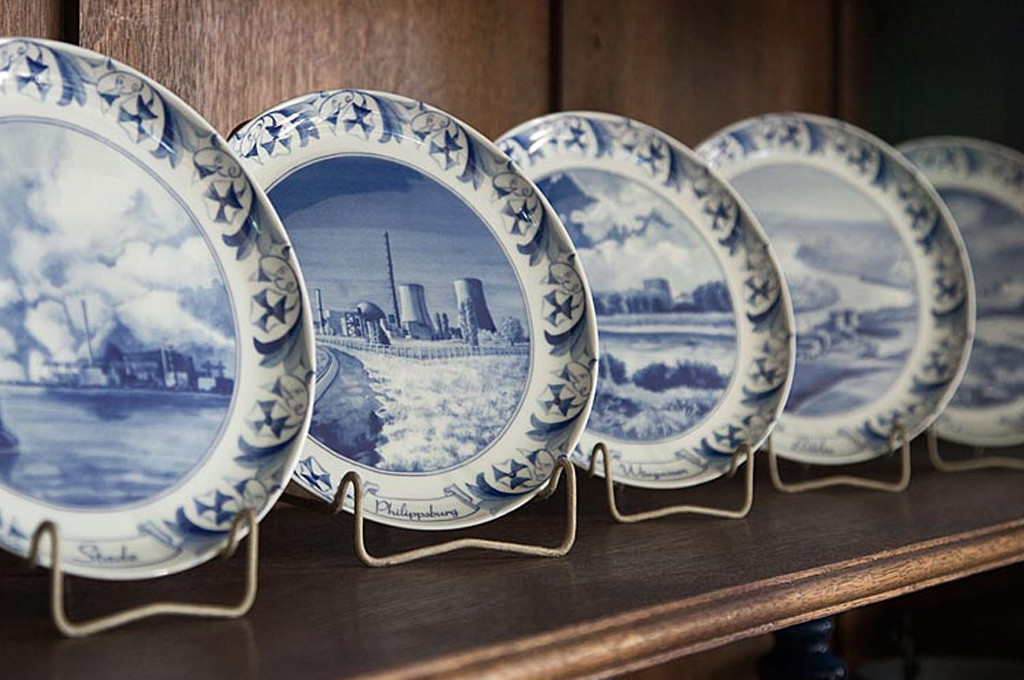 A display suggestion for a selection of plates from Atomteller, a range of porcelain wall plates with blue and white designs of German nuclear power plants in idyllic landscapes