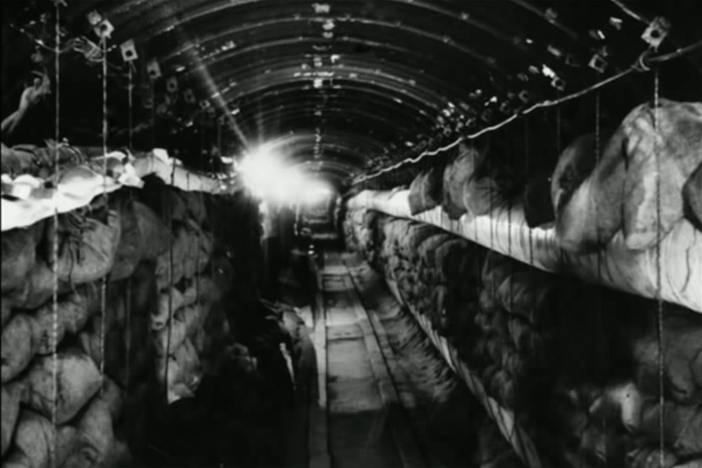 Berlin Spy Tunnel - A black and white photograph of the spy tunnel built under Altglienicke during the Cold War. The tunnel was used to tap Soviet communication lines between Berlin and Moscow as part of Operation Gold, a joint operation between MI6 and the CIA - Still from Spies Beneath Berlin