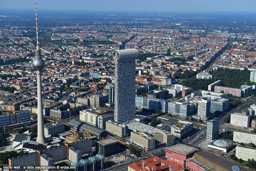 A photo showing a simulation of the 45,000 segments of the Berlin wall brought together to form a single 240-metre high segment placed in Alexanderplatz in Berlin next to the Fernsehturm (TV Tower) for scale - from Berlin Wall: A Data Visualization by Erdal Inci