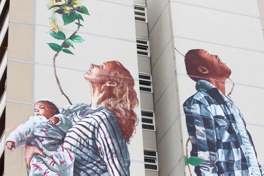 A woman holding a baby and a man look to the sky in the Cycle of Life mural by Australian street artist Fintan Magee arranged by Urban Nation at Neheimer Str.2 in Berlin Reinickendorf