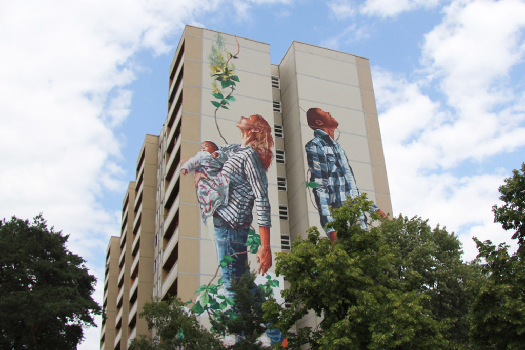 The figures of the Cycle of Life mural by Australian street artist Fintan Magee, arranged by Urban Nation at Neheimer Str.2 in Berlin Reinickendorf, emerge from the trees