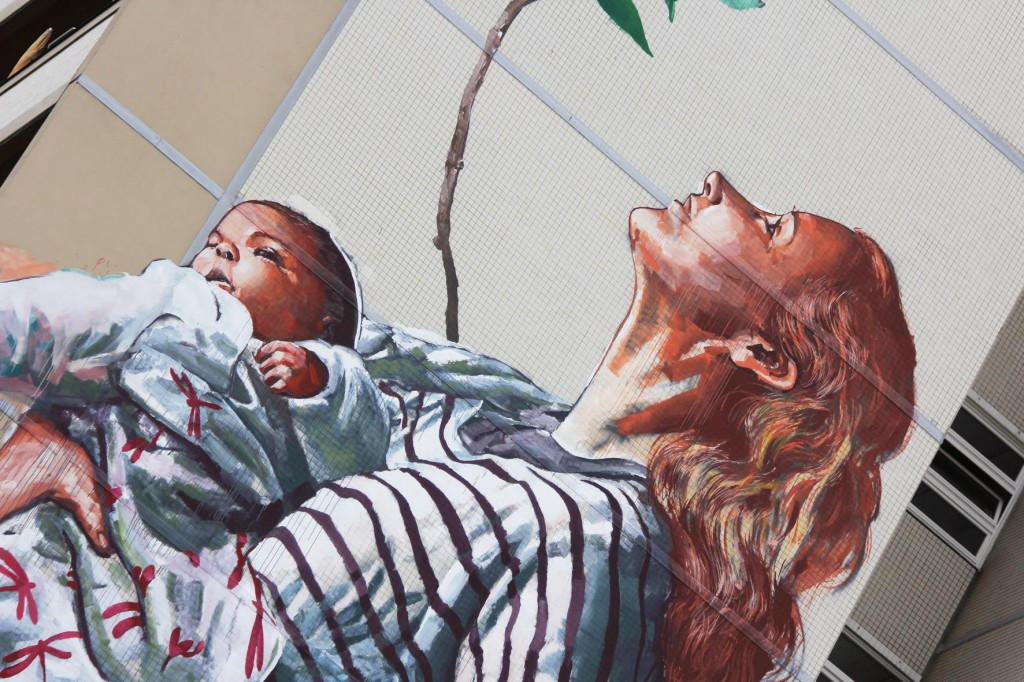 A woman holding a baby from the Cycle of Life mural by Australian street artist Fintan Magee arranged by Urban Nation at Neheimer Str.2 in Berlin Reinickendorf