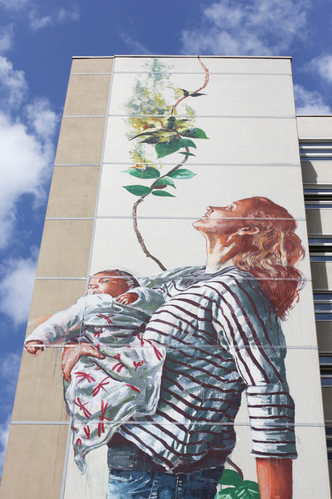 A woman holding a baby looks to the sky from the Cycle of Life mural by Australian street artist Fintan Magee arranged by Urban Nation at Neheimer Str.2 in Berlin Reinickendorf