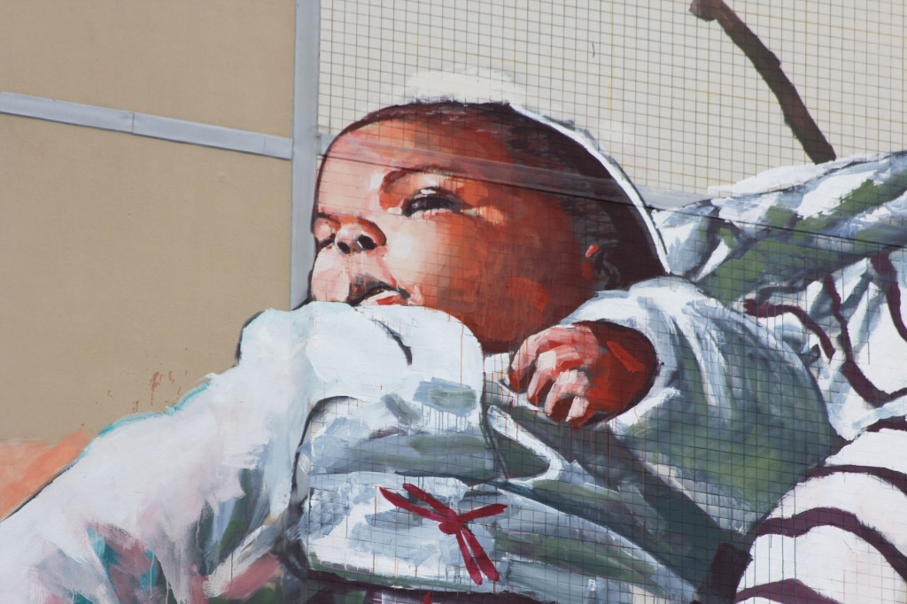 A baby from the Cycle of Life mural by Australian street artist Fintan Magee arranged by Urban Nation at Neheimer Str.2 in Berlin Reinickendorf