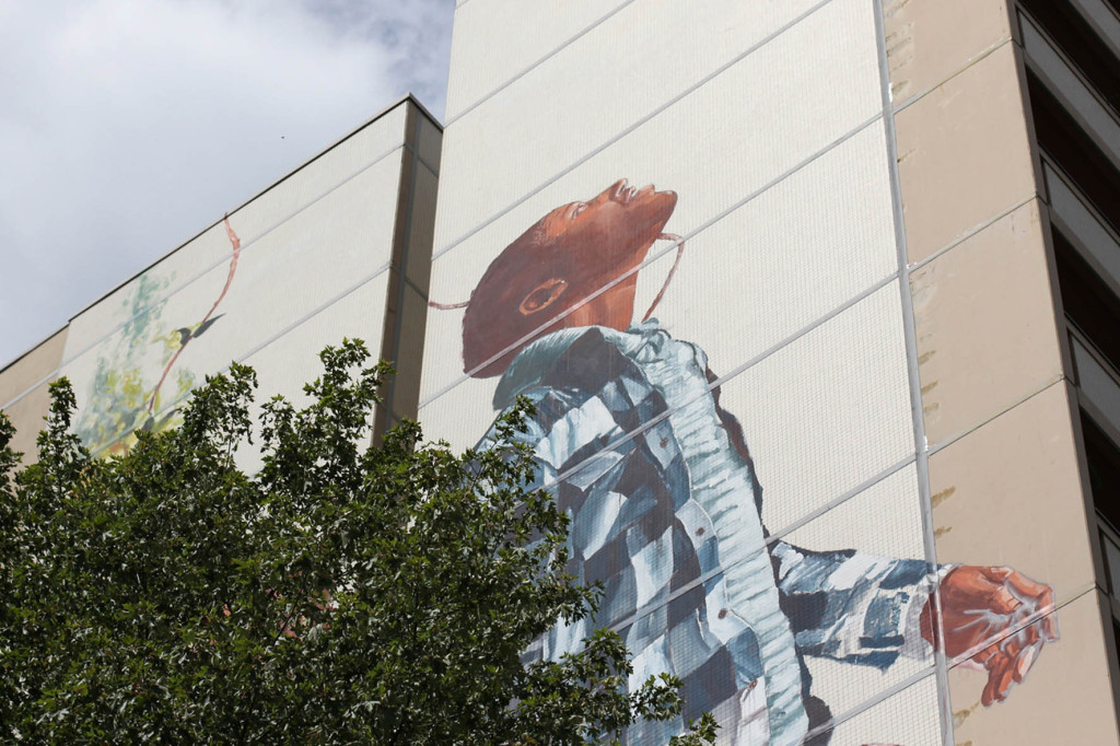 A man looking to the sky emerges from the tree - from the Cycle of Life mural by Australian street artist Fintan Magee arranged by Urban Nation at Neheimer Str.2 in Berlin Reinickendorf