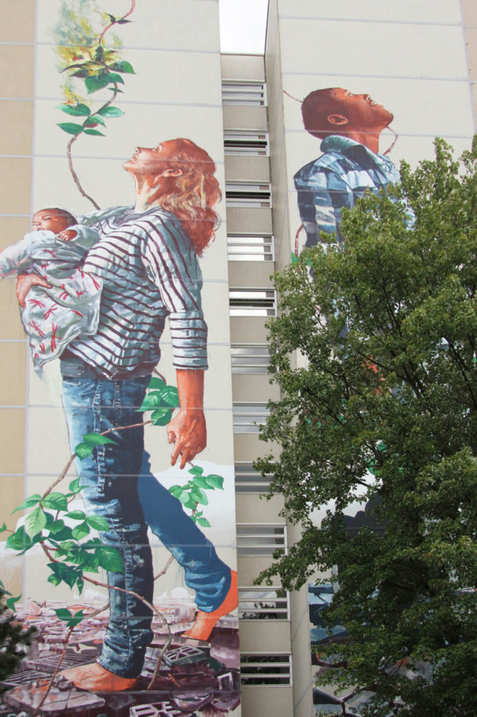 A woman holding a baby and a man looking to the sky - from the Cycle of Life mural by Australian street artist Fintan Magee arranged by Urban Nation at Neheimer Str.2 in Berlin Reinickendorf