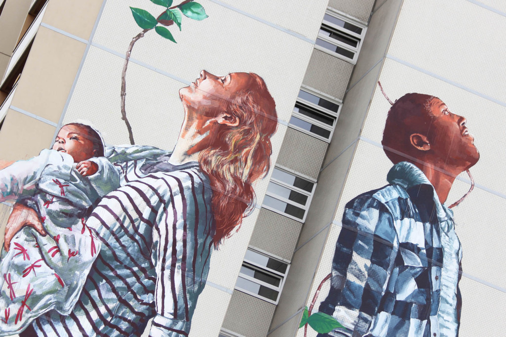Surrounded by plants, a woman holding a baby and a man stare at the sky - from the Cycle of Life mural by Australian street artist Fintan Magee arranged by Urban Nation at Neheimer Str.2 in Berlin Reinickendorf