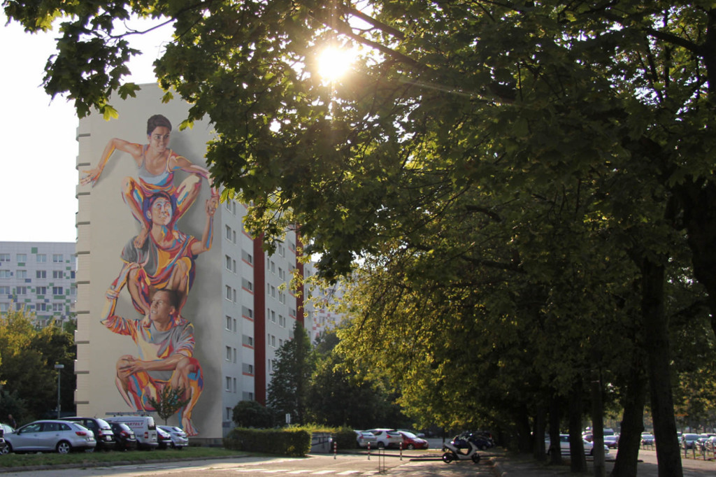 The JBAK Totem Mural on the side of the HOWOGE building at Landsberger Allee 228B in Lichtenberg in Berlin seen from under nearby trees