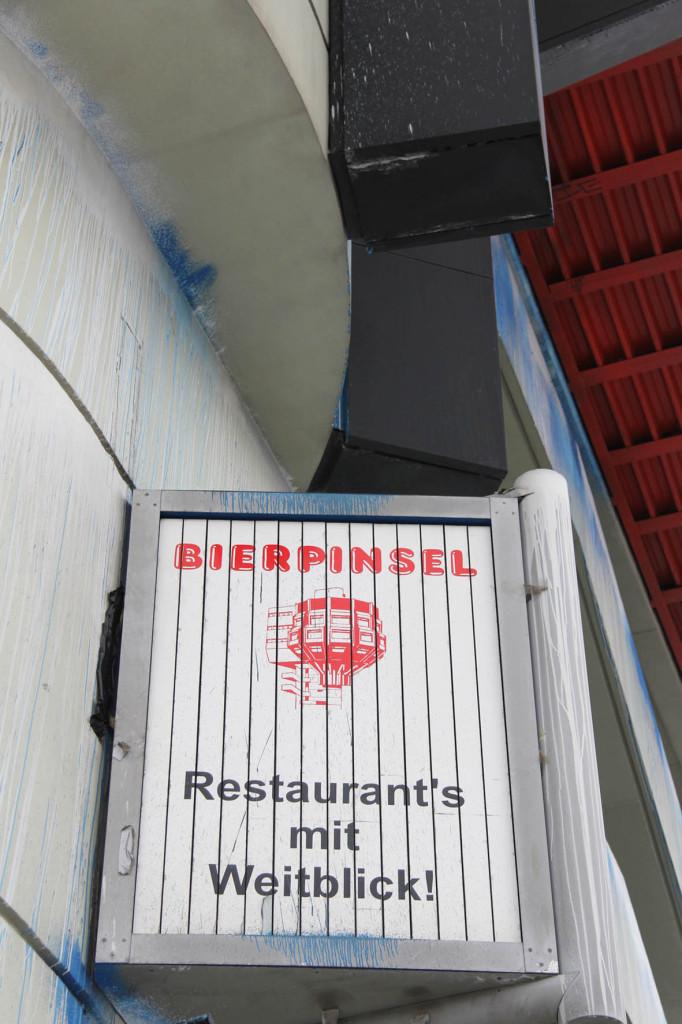 Ein Schild auf dem Bierpinsel, einem brutalistischen Turm in Berlin-Steglitz, das Restaurants mit Weitblick bewirbt