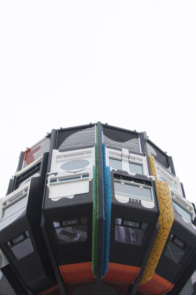 Die mehrfarbige Krone des Bierpinsels, einem brutalistischen Turm in Berlin-Steglitz, von der Schloßstraße betrachtet