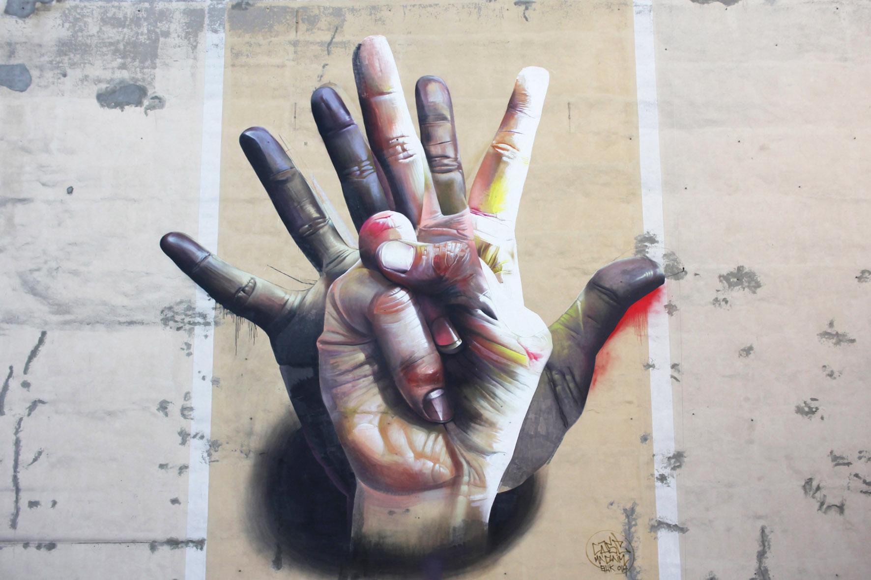 Das Street Art Mural Unter der Hand von CASE Maclaim mit bunten, überlappenden Händen an der Ecke Brückenstraße / Köpenicker Strasse in der Nähe des Eingangs zum U-Bahnhof Heinrich-Heine-Straße in Berlin