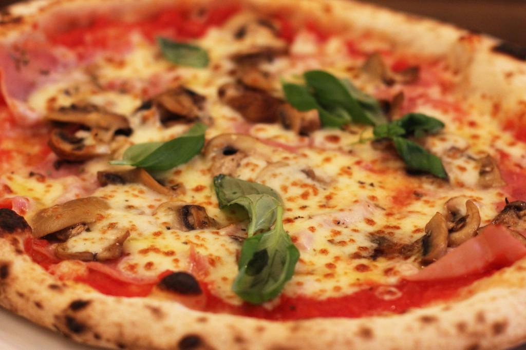 Ham, mushrooms, basil on a pizza at Zola Berlin Pizzeria in a Hinterhof (courtyard) on Paul-Lincke-Ufer in Kreuzberg