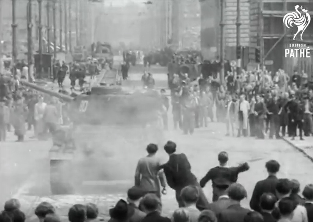East Berliners throw rocks at a Soviet tank during the riots of the 17 June 1953 Uprising on the streets of East Berlin - Still from Berlin Riots British Pathé Newsreel