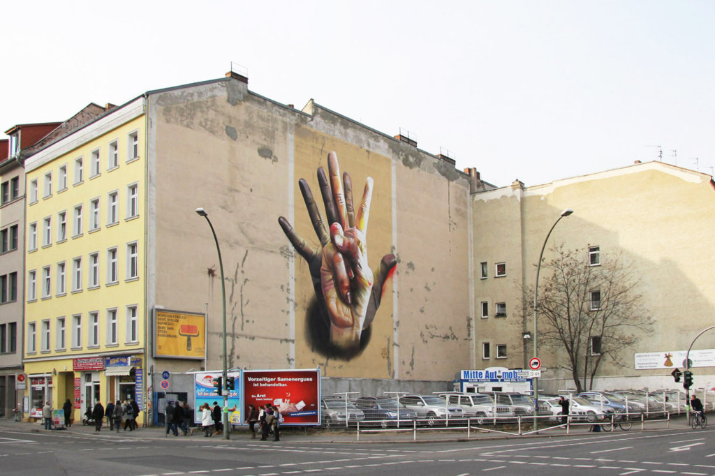 Wide angle view of the CASE Maclaim Unter der Hand Street Art Mural of colourful overlapping hands on the corner of Brückenstrasse and Köpenicker Strasse near the entrance to U-Bahnhof Heinrich-Heine-Strasse in Berlin