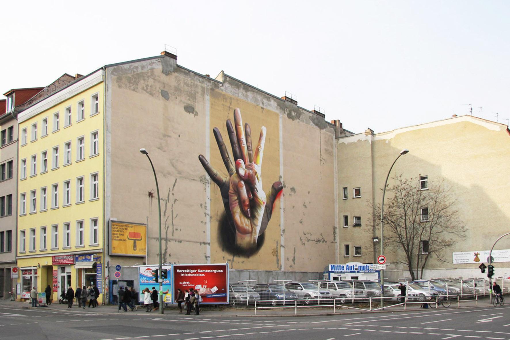 Weitwinkel Anblick von dem Street Art Mural Unter der Hand von CASE Maclaim mit bunten, überlappenden Händen an der Ecke Brückenstraße / Köpenicker Strasse in der Nähe des Eingangs zum U-Bahnhof Heinrich-Heine-Straße in Berlin