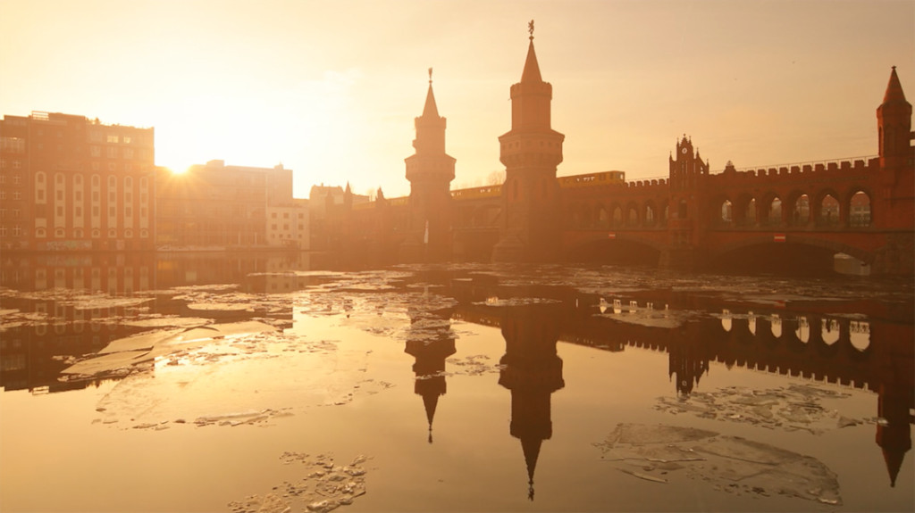 The Oberbaumbrücke bathed in a soft orange glow with ice on the Spree during a Berlin winter from the video, Berlin City by Matthias Makarinus