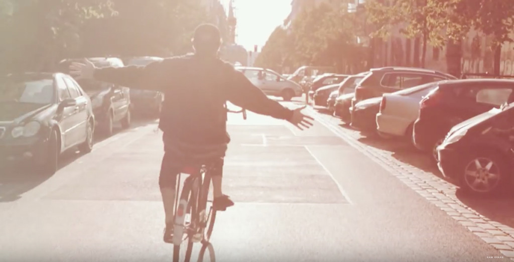Sam Evans riding a bike through the streets of Berlin on a bright and sunny day - Screenshot from Berlin Vibes by Sam Evans