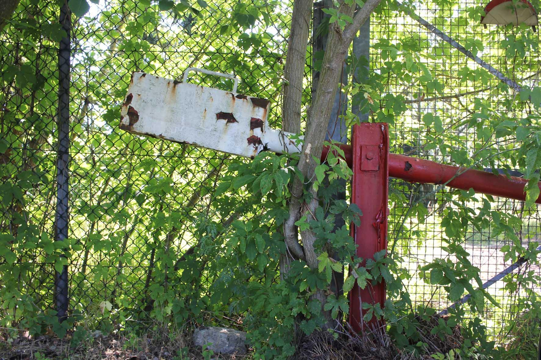 Eine rostige Barriere auf der Osdorfer Strasse an einem Grenzzaun Parks Range und Doughboy City - ein ehemaliger Truppenübungsplatz der US Army Berlin Brigade