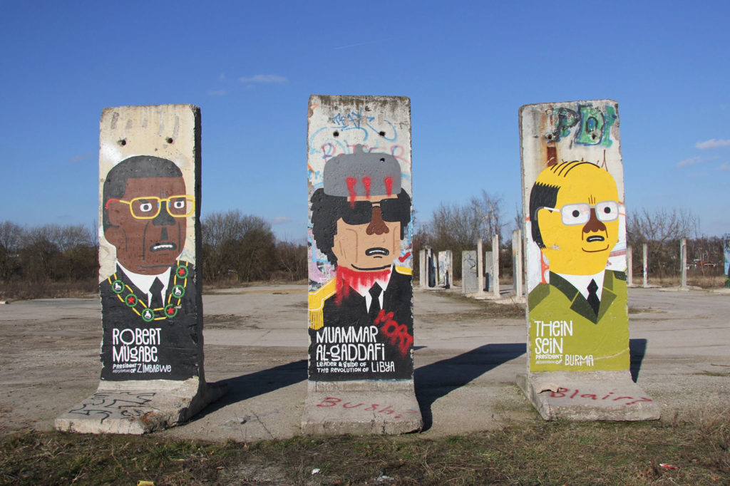 Berlin Wall Graveyard - Painted sections of the Berlin wall on waste ground in Teltow that will soon be part of the Teltow Marina - a despots series by a Japanese artist including Robert Mugabe, Mummer Al-Gadaffi and Thein Sein - Photo February 2014