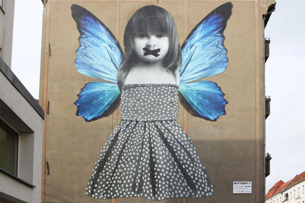 Butterfly Mural - a little girl in a polka dot dress with bright blue butterfly wings - Street Art by Michelle Tombolini in Berlin at Krossener Strasse 36 in Friedrichshain, seen from Boxhagener Strasse