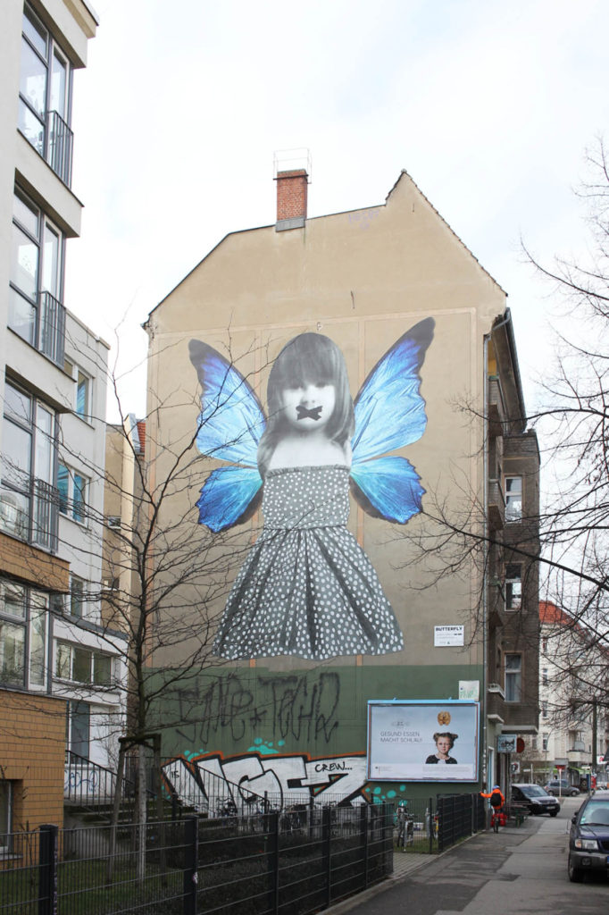 Butterfly Mural - Street Art by Michelle Tombolini in Berlin seen through the trees on Boxhagener Strasse in Friedrichshain