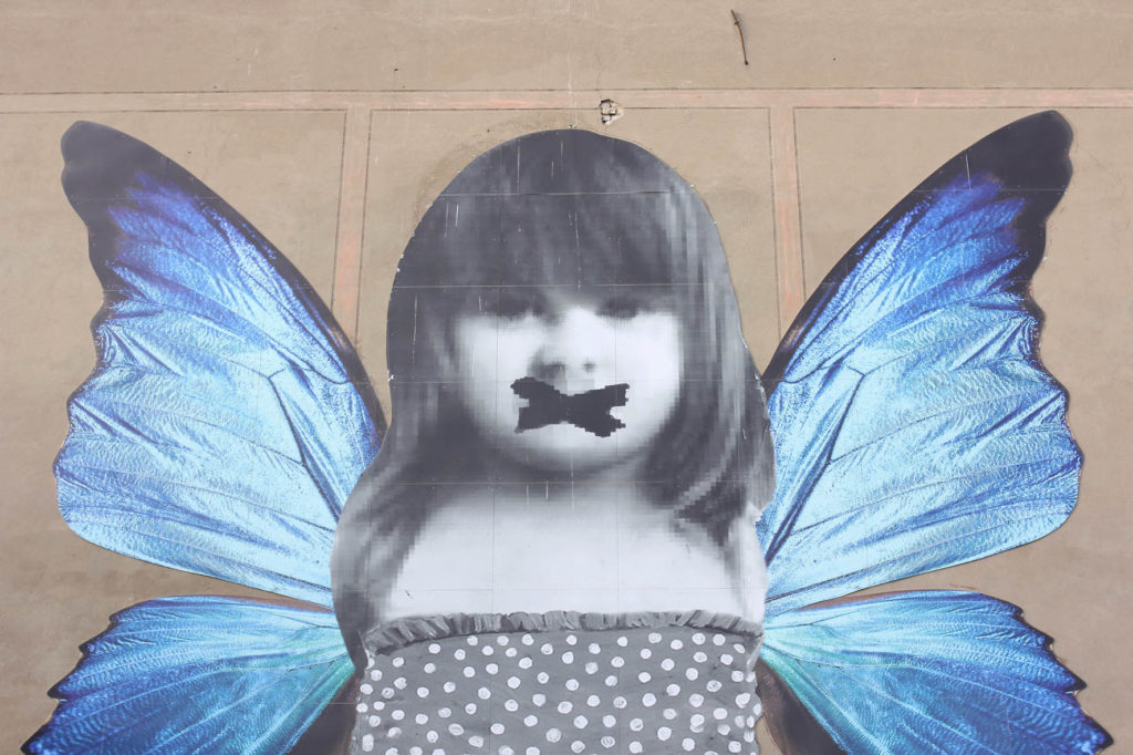 Close up of Butterfly Mural - a little girl in a polka dot dress with bright blue butterfly wings - Street Art by Michelle Tombolini in Berlin