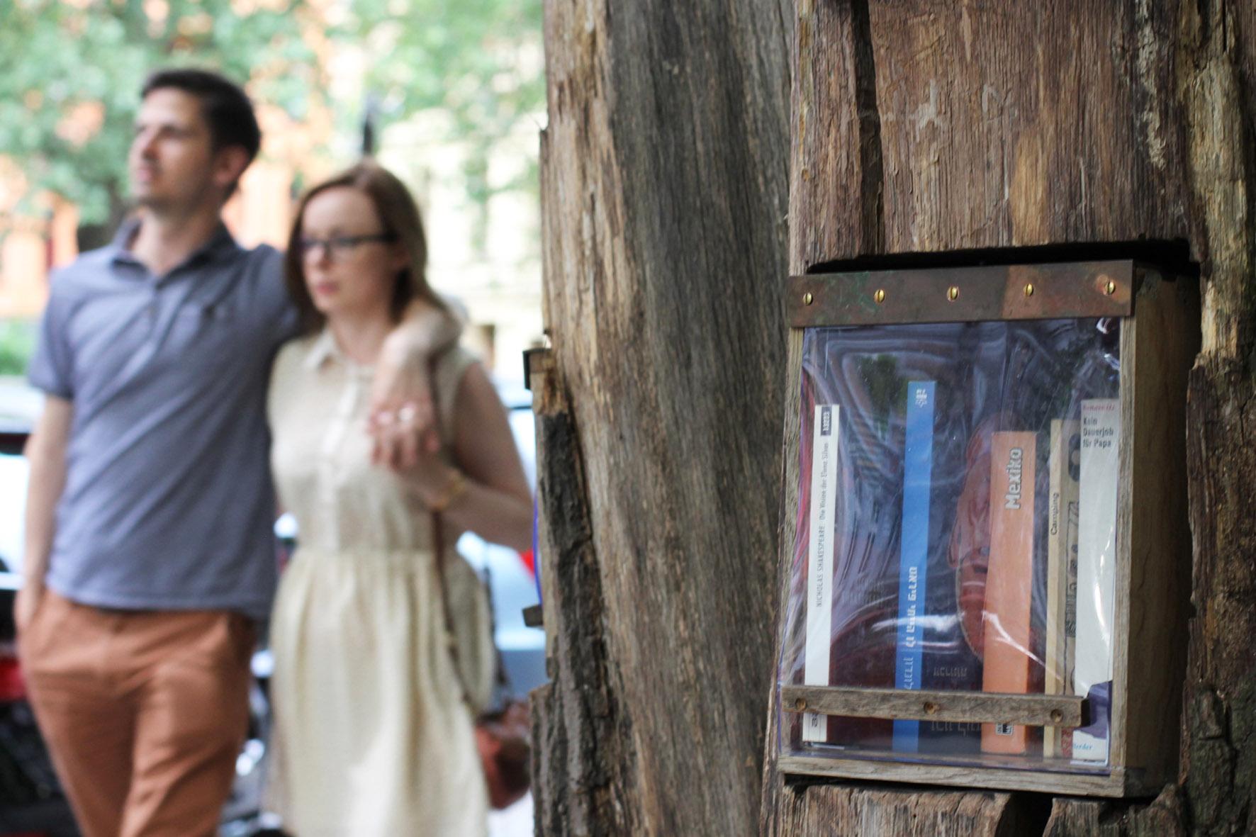Ein Pärchen läuft an dem Bücherwald vorbei - Eine Bibliothek mit Regalen, die in Stämme geschnitzt sind, die zusammen verschraubt wurden, um einem Baum zu ähneln - auf der Sredzkistrasse in Berlin Prenzlauer Berg