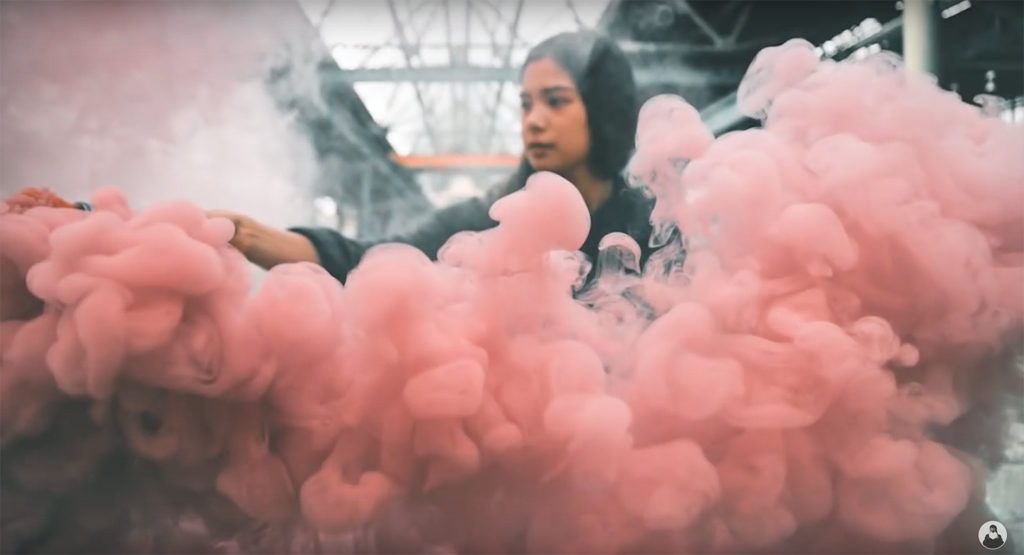Marisa Hampe surrounded by pink smoke at an abandoned warehouse in Berlin by Jeisson Martin - still from '#EXPLOREEVERYTHING in the underground subway system of Berlin' on YouTube