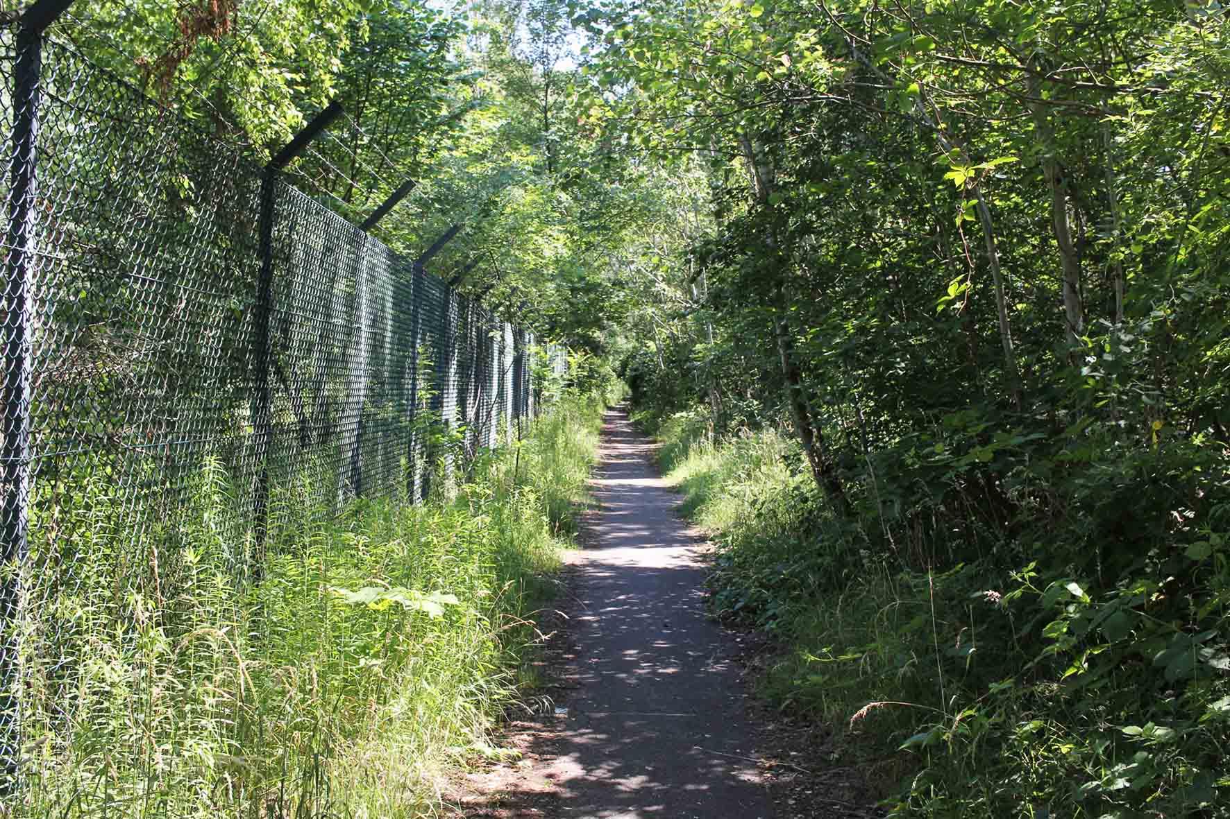 Ein Weg und der Grenzzaun parallel zur ehemalige Route der Berliner Mauer am Parks Range und Doughboy City - ein ehemaliger Truppenübungsplatz der US Army Berlin Brigade