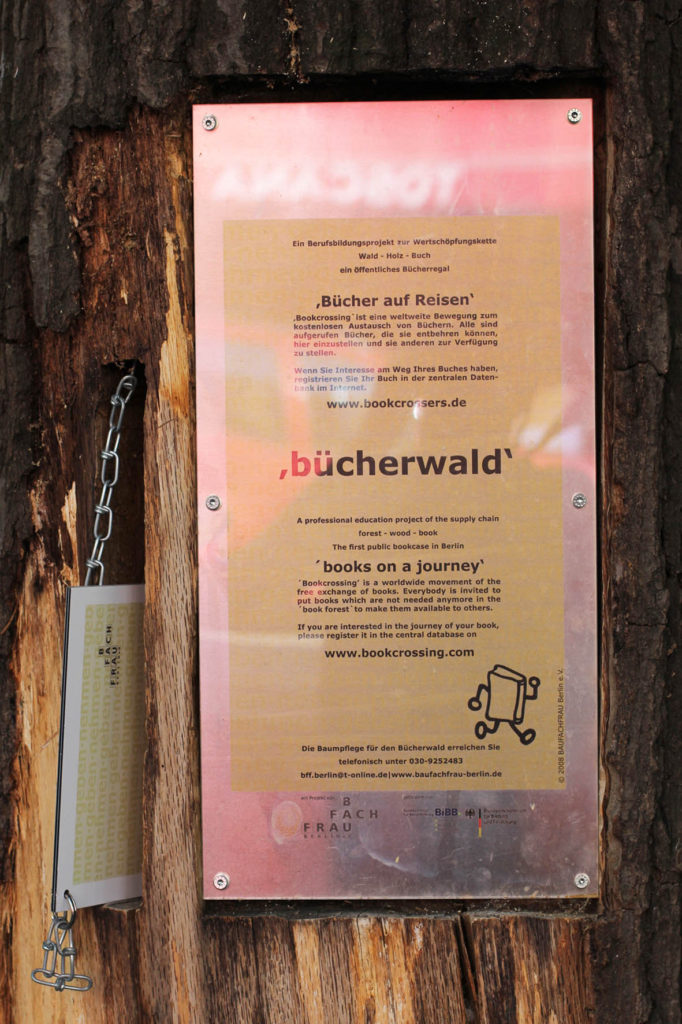 A plaque on the Bücherwald (book forest) - a lending library with shelves carved into logs bolted together to resemble a tree on Sredzkistrasse in Berlin Prenzlauer Berg. A professional education project of the supply chain forest – wood – book The first public bookcase in Berlin