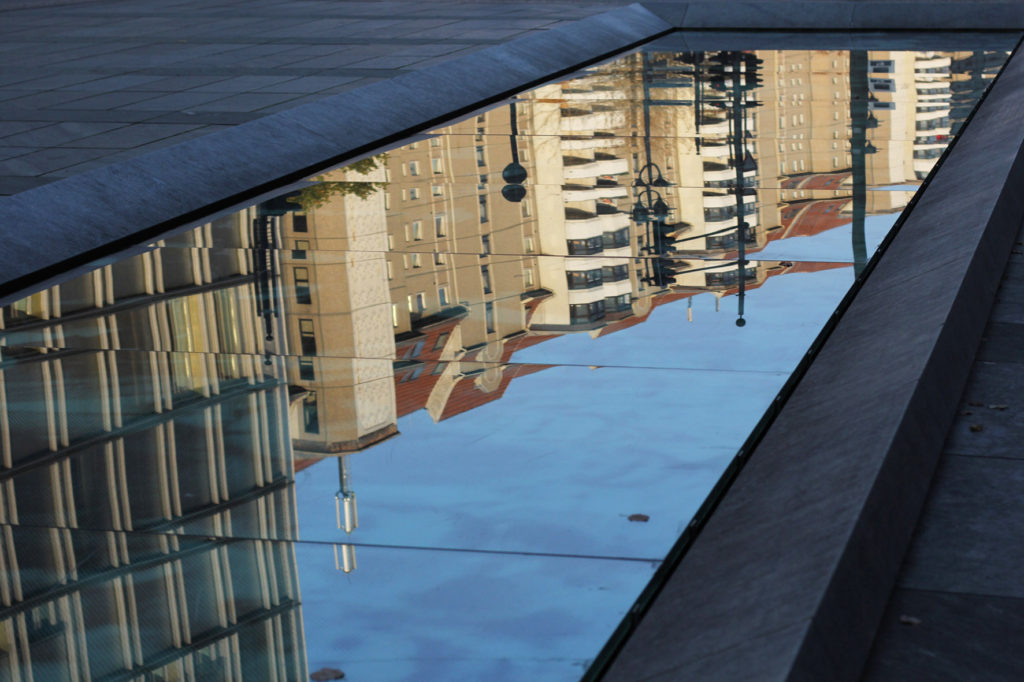 Buildings on Leipziger Strasse reflected in the glass of the 17 June Memorial by Wolfgang Rüppel in Berlin