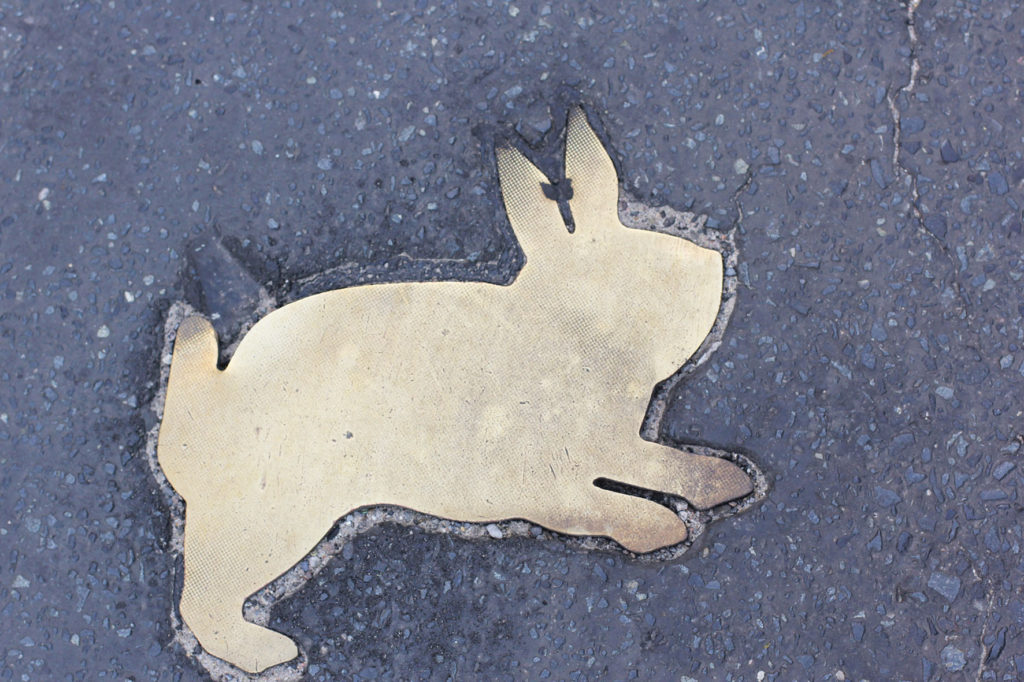 A springing brass rabbit on the road of the Kaninchenfeld (Rabbit Field), a memorial to the rabbits that lived on the Berlin Wall death strip by Karla Sachse at the site of a former border crossing point on the Chausseestrasse in Berlin