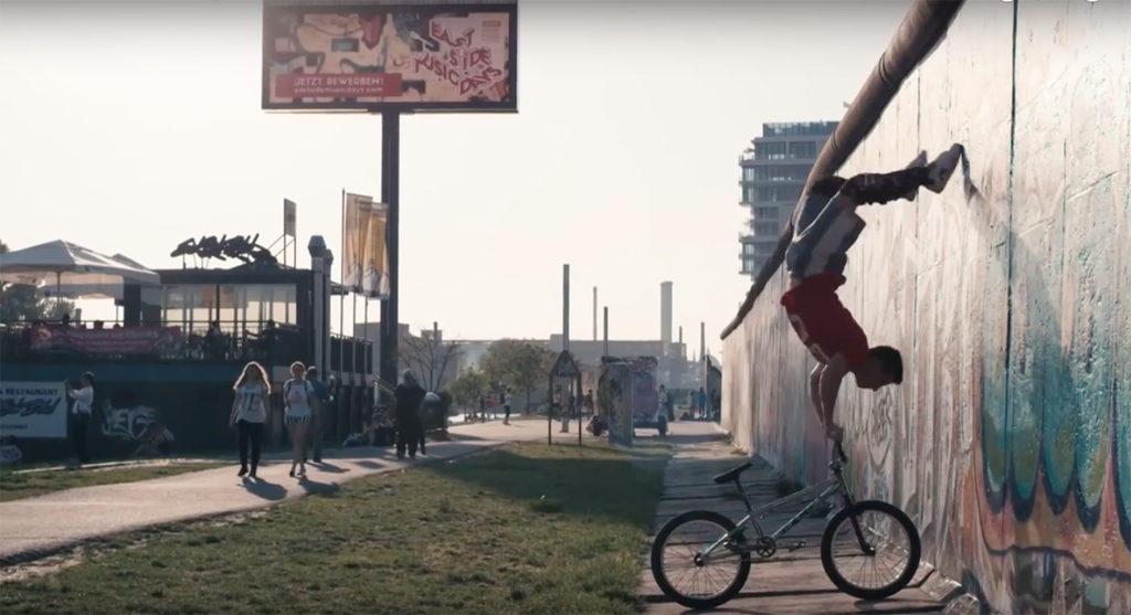 Tim Knoll in Berlin - Tim Knoll does a handstand on his BMX against the Berlin wall at the East Side Gallery - still from BMX Meets Parkour | Unthinkable Bike Tricks video for Red Bull