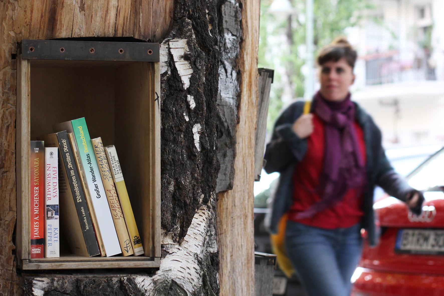 Eine Frau läuft an dem Bücherwald vorbei - Eine Bibliothek mit Regalen, die in Stämme geschnitzt sind, die zusammen verschraubt wurden, um einem Baum zu ähneln - auf der Sredzkistrasse in Berlin Prenzlauer Berg
