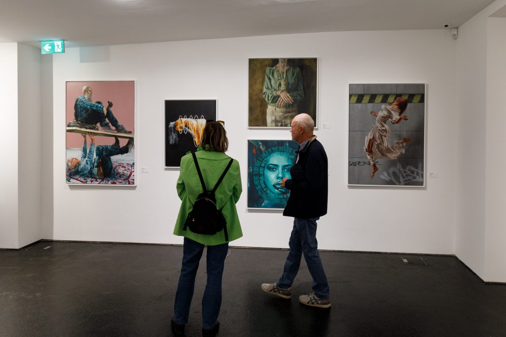 Visitors admire works by Fintan Magee, James Bullough and others at Urban Nation Museum for Urban Contemporary Art in Berlin
