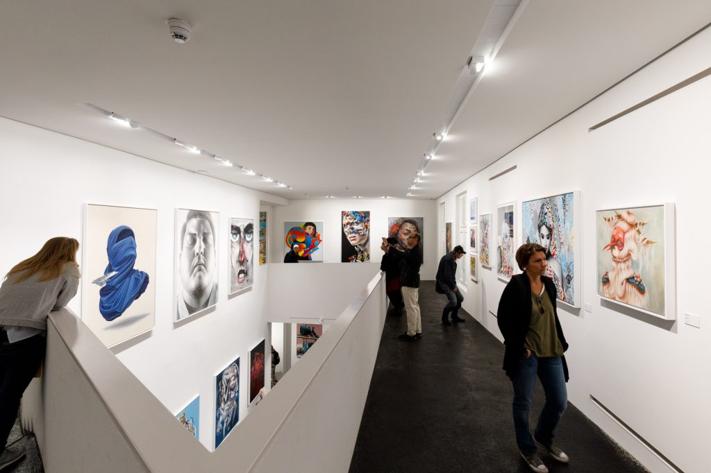 Besucher bewundern Kunstwerke von El Mac, Anthony Lister and Miss Van und anderen von dem Steg im Urban Nation Museum for Urban Contemporary Art in Berlin