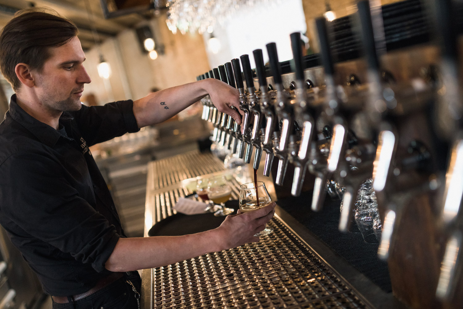 A barman pours a beer at Stone Brewing Berlin, the European headquarters of the US craft brewer in the former Marienfedorf gasworks - Photo Credit ©2017 Stefan Haehnel