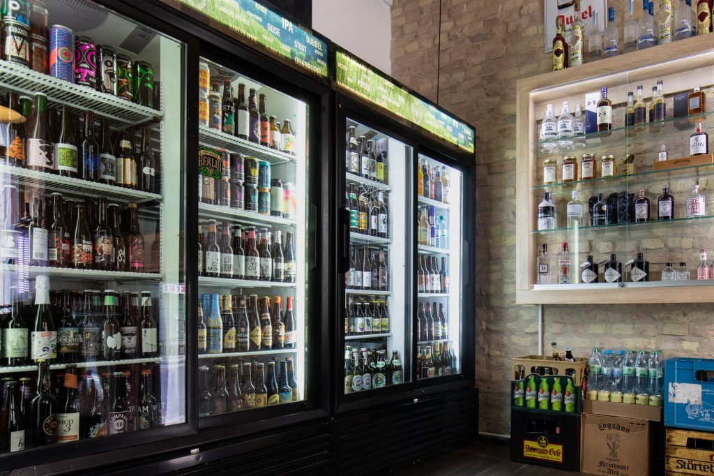 Fridges full of beer and spirits in a cabinet at Biererei Store Berlin - a craft beer bottle shop in Kreuzberg