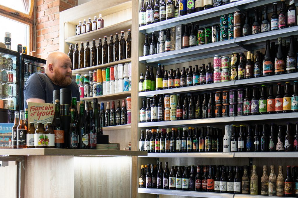 Martin giving advice to a customer scouring the shelves at Biererei Store Berlin - a craft beer bottle shop in Kreuzberg