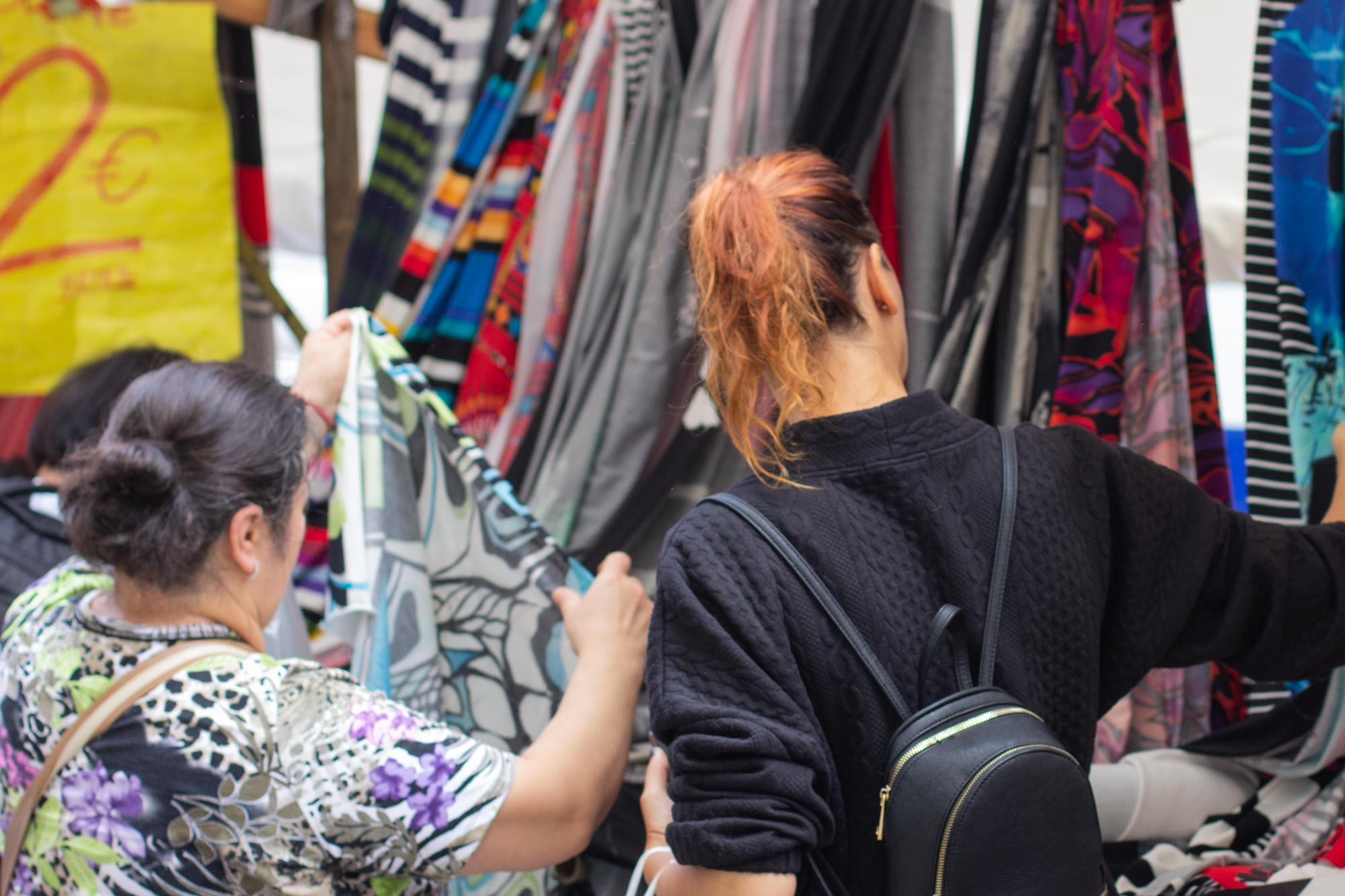 Zwei Frauen begutachten die Stoffe an einem Stoffstand auf dem sehr bunten türkischen Markt am Maybachufer in Berlin Neukölln