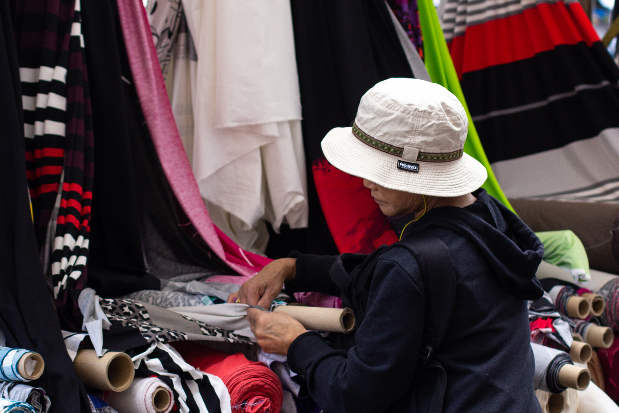 Eine Frau begutachtet die Stoffe an einem Stoffstand auf dem sehr bunten türkischen Markt am Maybachufer in Berlin Neukölln