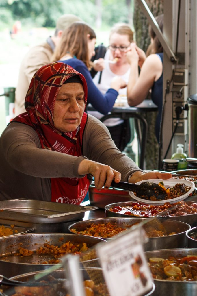 A lady serves up food at the Mamas Food Manufaktur stall at the very colourful Turkish Market on Maybachufer in Berlin Neukölln