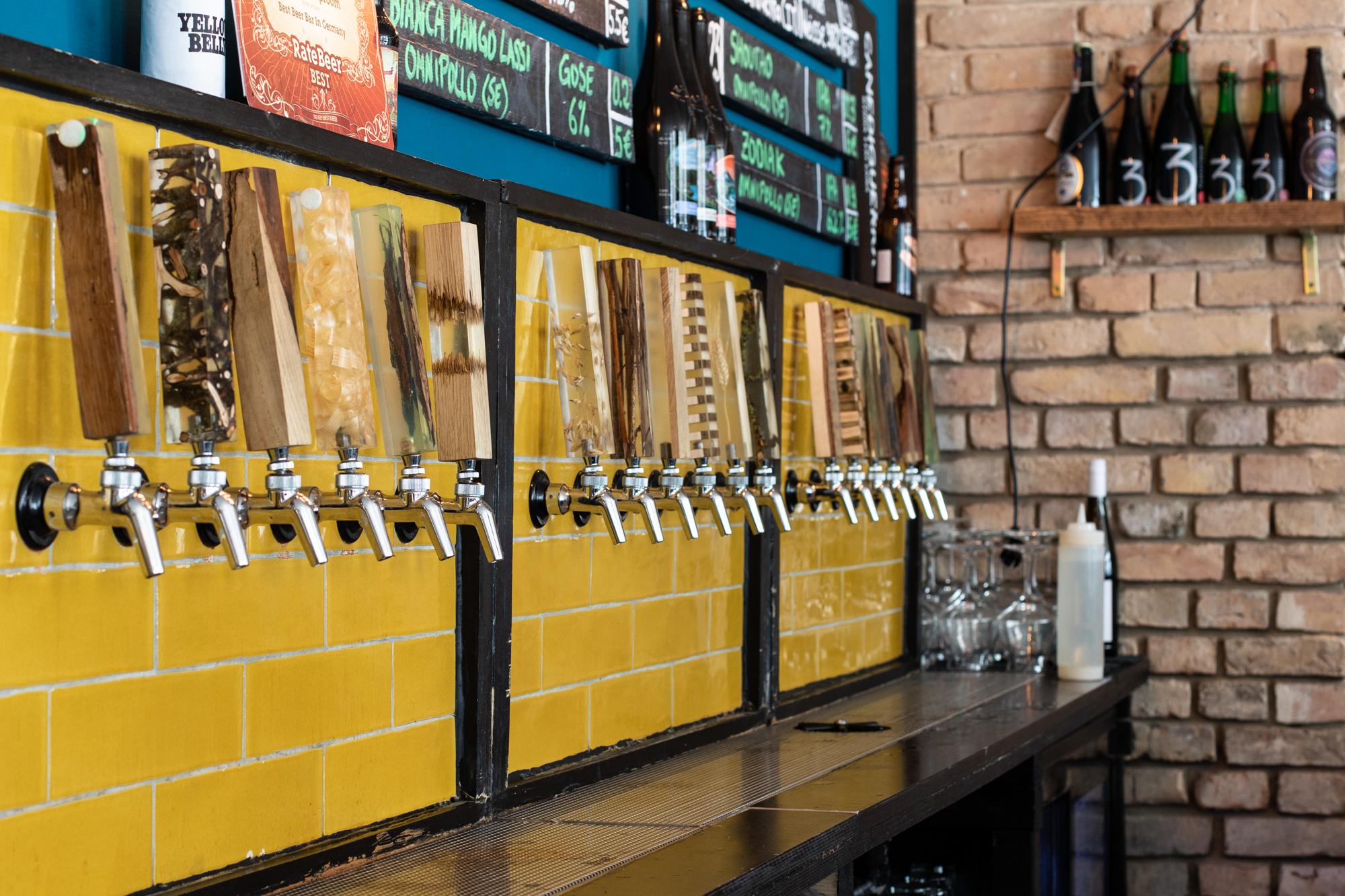 Die Zapfhähne und die charakteristischen gelben Fliesen im Protokoll Taproom Berlin, eine Craft Beer Bar mit 24 Zapfhähne in Berlin Friedrichshain