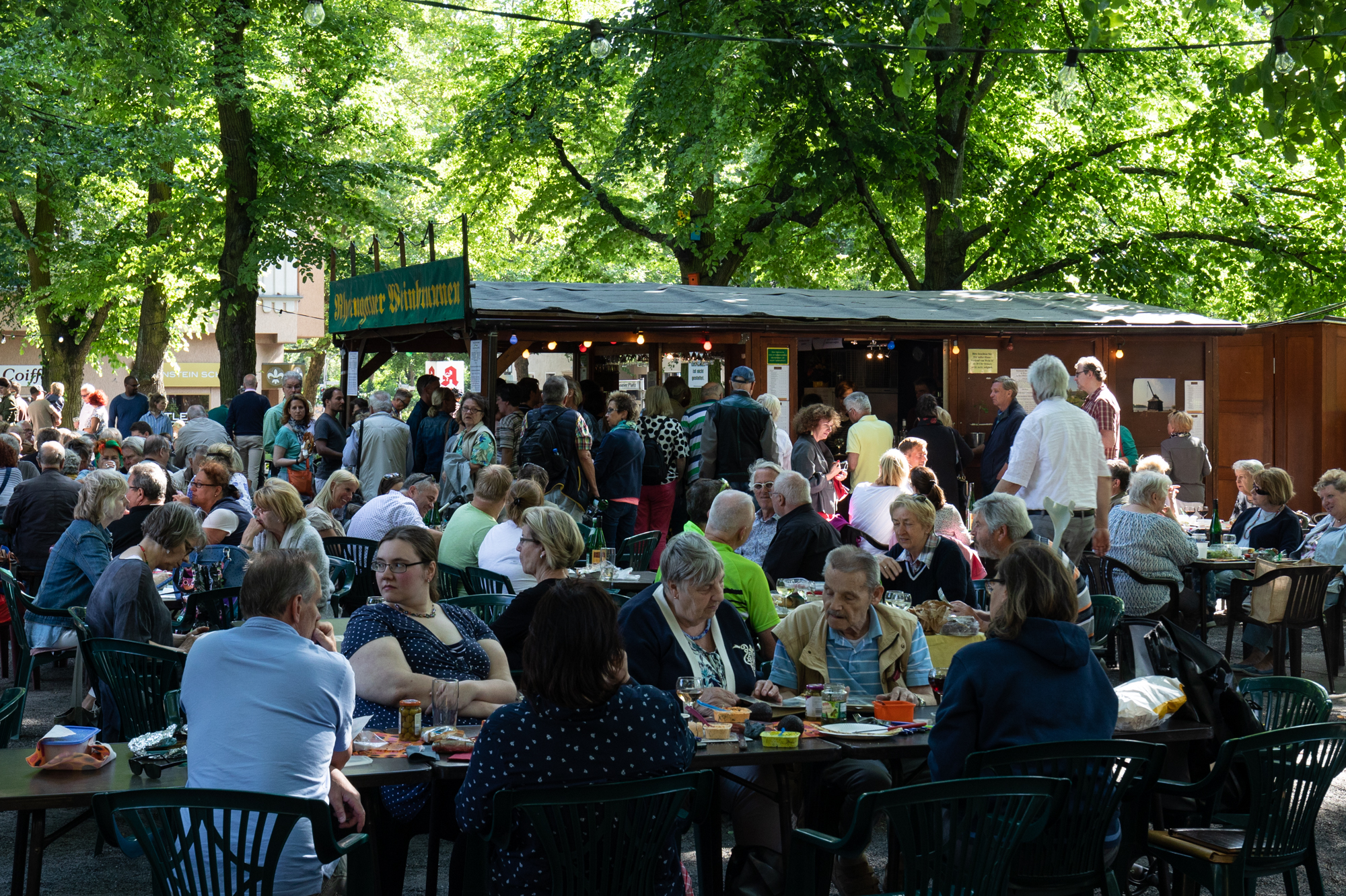 Guests enjoying their drinks at the Rheingauer Weinbrunnen - a wooden hut serving wines from Rheingau-Taunus district of Hesse on the Rüdesheimer Platz in Berlin Wilmersdorf