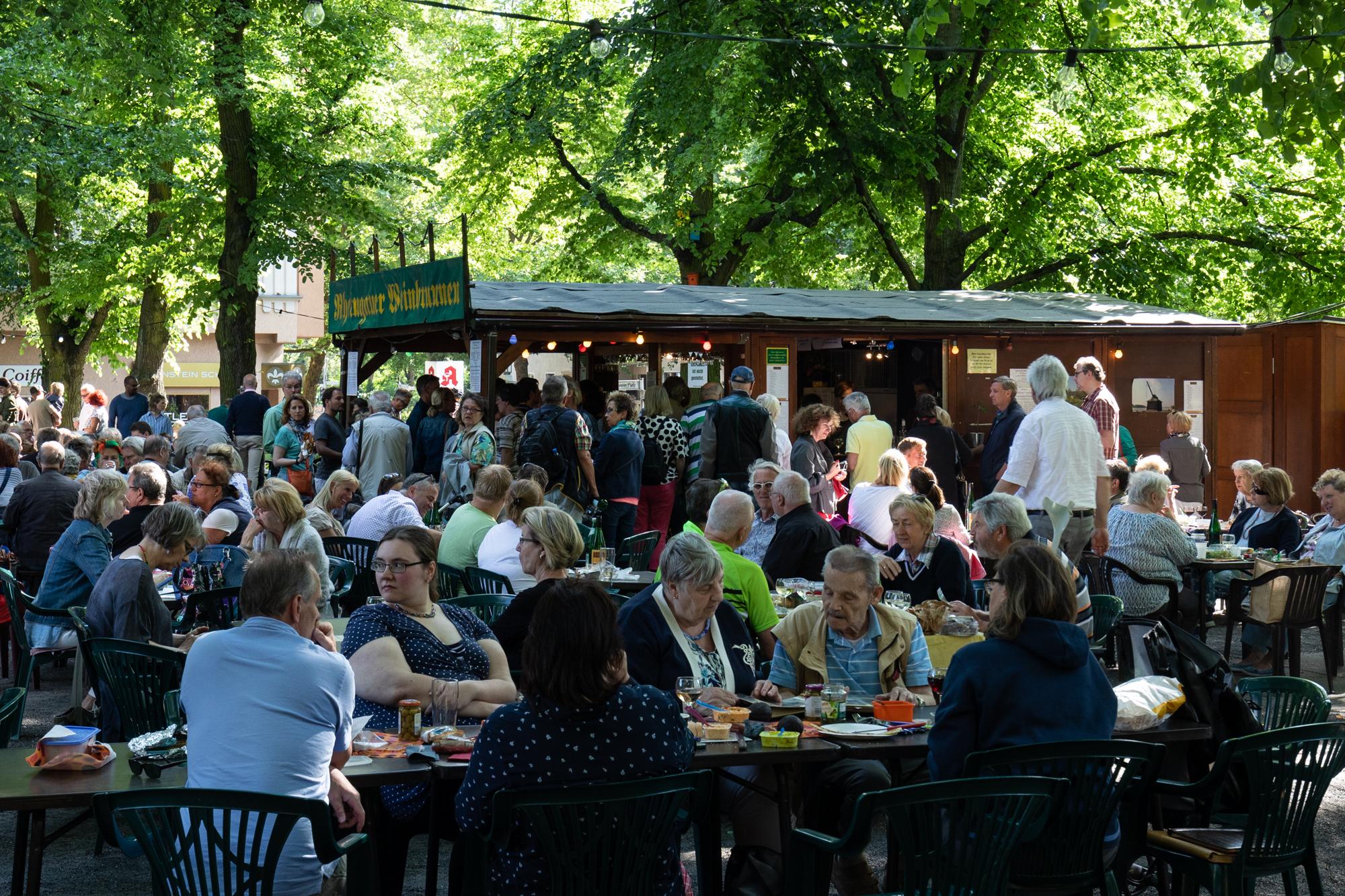 Gäste geniessen ihren Wein am Rheingauer Weinbrunnen - eine Holzhütte, die Weine aus dem Rheingau-Taunus in Hessen am Rüdesheimer Platz in Berlin Wilmersdorf serviert