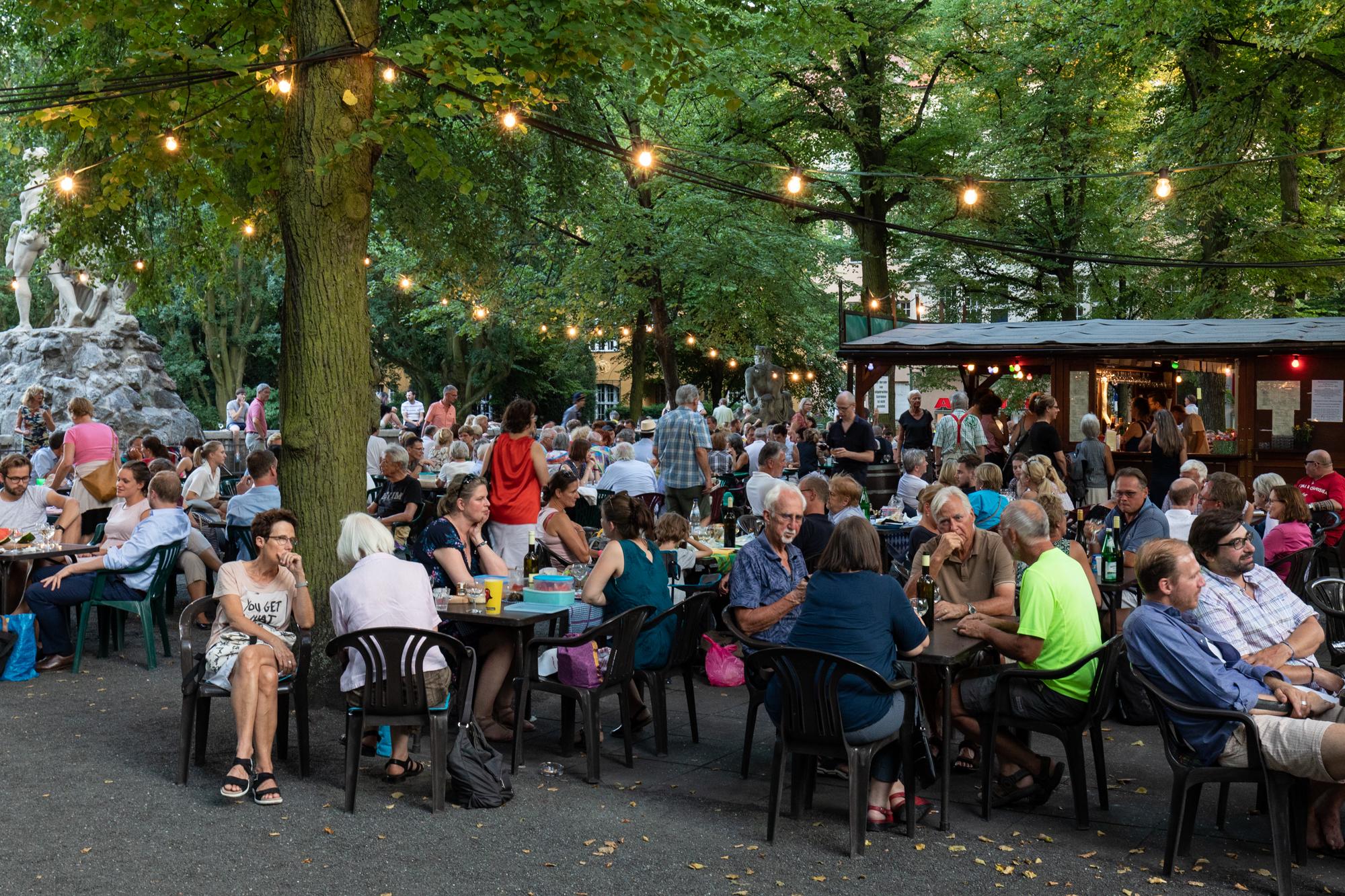 Gäste unter den Lichtern in den Bäumen am Rheingauer Weinbrunnen - eine Holzhütte, die Weine aus dem Rheingau-Taunus in Hessen am Rüdesheimer Platz in Berlin Wilmersdorf serviert