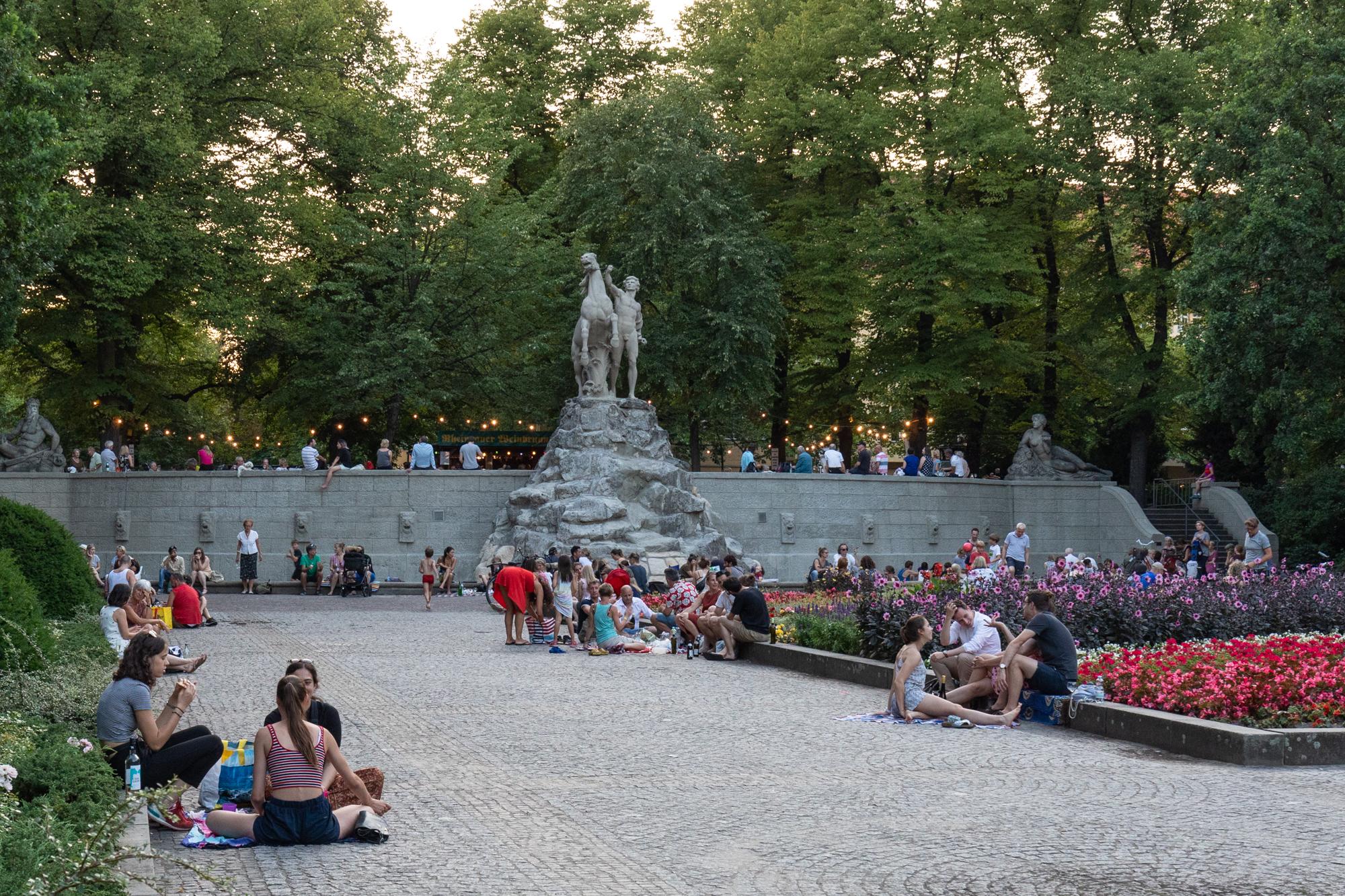 Gäste sitzen auf dem Rüdesheimer Platz vor dem Rheingauer Weinbrunnen - eine Holzhütte, die Weine aus dem Rheingau-Taunus in Hessen am Rüdesheimer Platz in Berlin Wilmersdorf serviert
